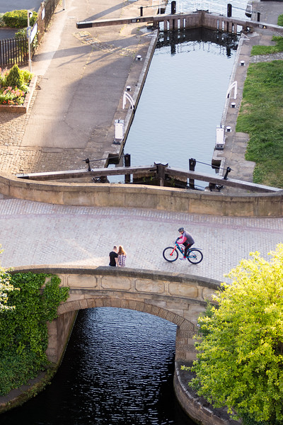 Cyclist passing couple on canal bridge