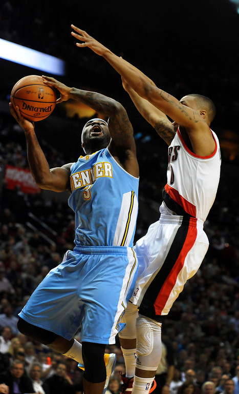. Denver Nuggets point guard Ty Lawson (3) drives to the basket on Portland Trail Blazers point guard Damian Lillard (0) during the first quarter of their NBA basketball game in Portland, Oregon, February 27, 2013.  REUTERS/Steve Dykes