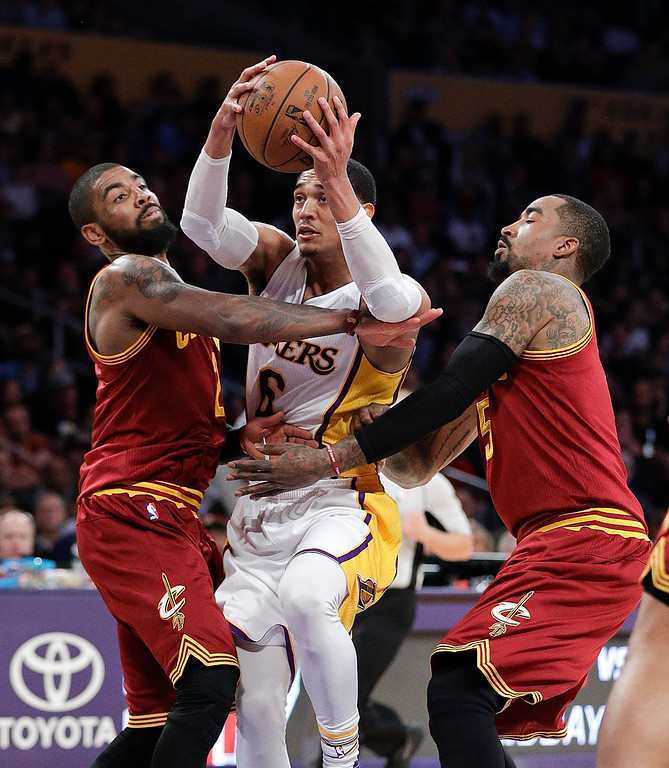. Los Angeles Lakers\' Jordan Clarkson, center, is double-teamed by Cleveland Cavaliers\' Kyrie Irving, left, and J.R. Smith during the first half of an NBA basketball game Sunday, March 19, 2017, in Los Angeles. (AP Photo/Jae C. Hong)
