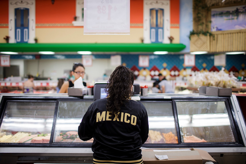 . Daniela Dominguez, an employee at Mi Pueblo Food Center wears a Mexican national soccer team\'s jacket on July 24, 2013 in San Jose. The Bay Area supermarket chain filed for Chapter 11 bankruptcy protection Monday, citing a dispute with its primary lender, Wells Fargo. (Dai Sugano/Bay Area News Group)