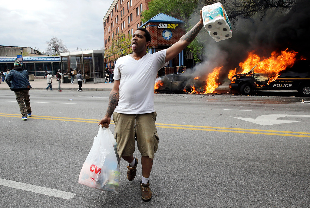 . A man carries items from a store as police vehicles burn, Monday, April 27, 2015, after the funeral of Freddie Gray in Baltimore. Gray died from spinal injuries about a week after he was arrested and transported in a Baltimore Police Department van. (AP Photo/Patrick Semansky)