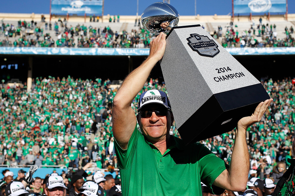 . DALLAS, TX - JANUARY 01:  Head Coach Dan McCarney of the North Texas Mean Green holds up the trophy after defeating the UNLV Rebels in the Heart of Dallas Bowl at Cotton Bowl Stadium on January 1, 2014 in Dallas, Texas. The North Texas Mean Green defeated the UNLV Rebels 36-14.  (Photo by Sarah Glenn/Getty Images)