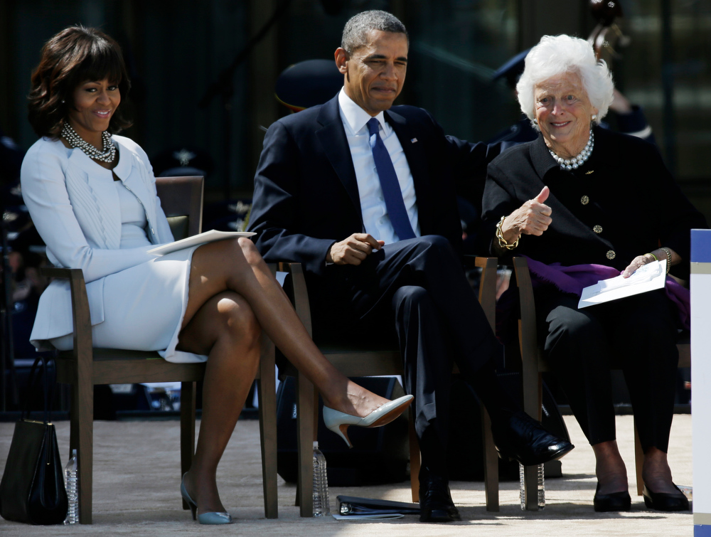 Description of . President Barack Obama and First Lady Michelle Obama watch as former first lady Barbara Bush gives the thumbs up to guests during the dedication of the George W. Bush Presidential Center Thursday, April 25, 2013, in Dallas. (AP Photo/David J. Phillip)