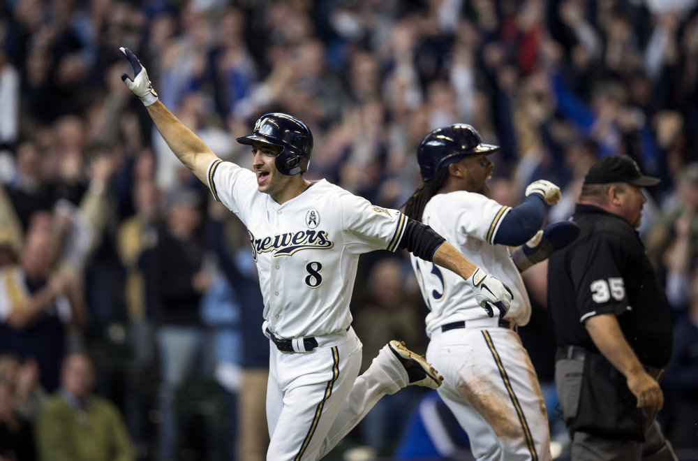 . Ryan Braun #8 and Rickie Weeks #23 of the Milwaukee Brewers score in the eighth inning against the Colorado Rockies on opening day at Miller Park on April 1, 2013 in Milwaukee, Wisconsin.  The Milwaukee Brewers defeated the Colorado Rockier 5-4.  (Photo by Tom Lynn/Getty Images)