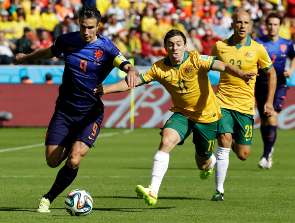 . Australia\'s Tommy Oar (11) tries to push Netherlands\' Robin van Persie (9) away from the ball during the group B World Cup soccer match between Australia and the Netherlands at the Estadio Beira-Rio in Porto Alegre, Brazil, Wednesday, June 18, 2014.  (AP Photo/Fernando Vergara)
