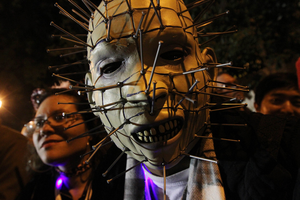 . Wearing a mask, Marcos Villegas, of the Bronx borough of New York, center, poses for a photograph as he watches the Village Halloween Parade on Thursday Oct. 31, 2013, in New York.  (AP Photo/Tina Fineberg)
