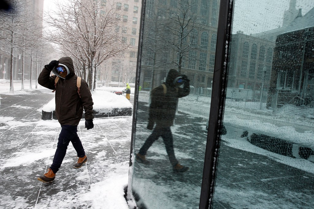 . A pedestrian is reflected in a building\'s plate glass window during a snowstorm, Tuesday, March 13, 2018, in Boston. (AP Photo/Michael Dwyer)