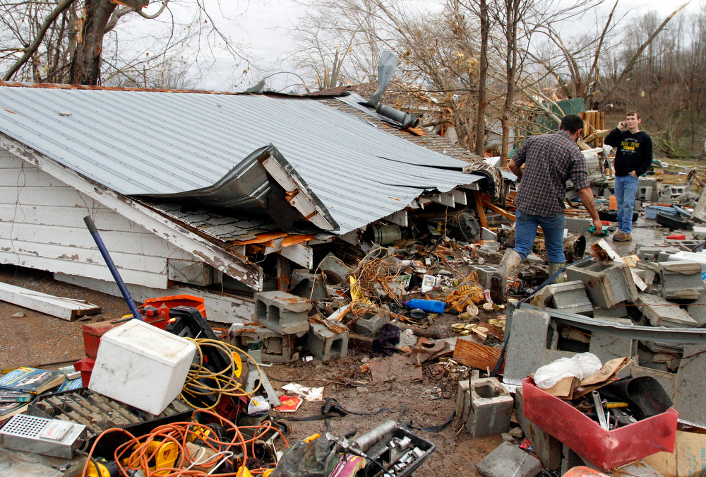 Description of . Residents search through debris after a storm ripped through Coble, Tenn. early Wednesday, Jan. 30, 2013. A large storm system packing high winds, hail and at least one tornado tore across a wide swath of the South and Midwest on Wednesday, killing one person, blacking out power to thousands and damaging homes. (AP Photo/Butch Dill)