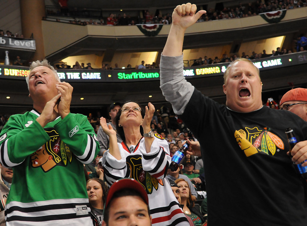 . A trio of Chicago fans cheer their team\'s second goal against the Wild in the second period. (Pioneer Press: John Autey)