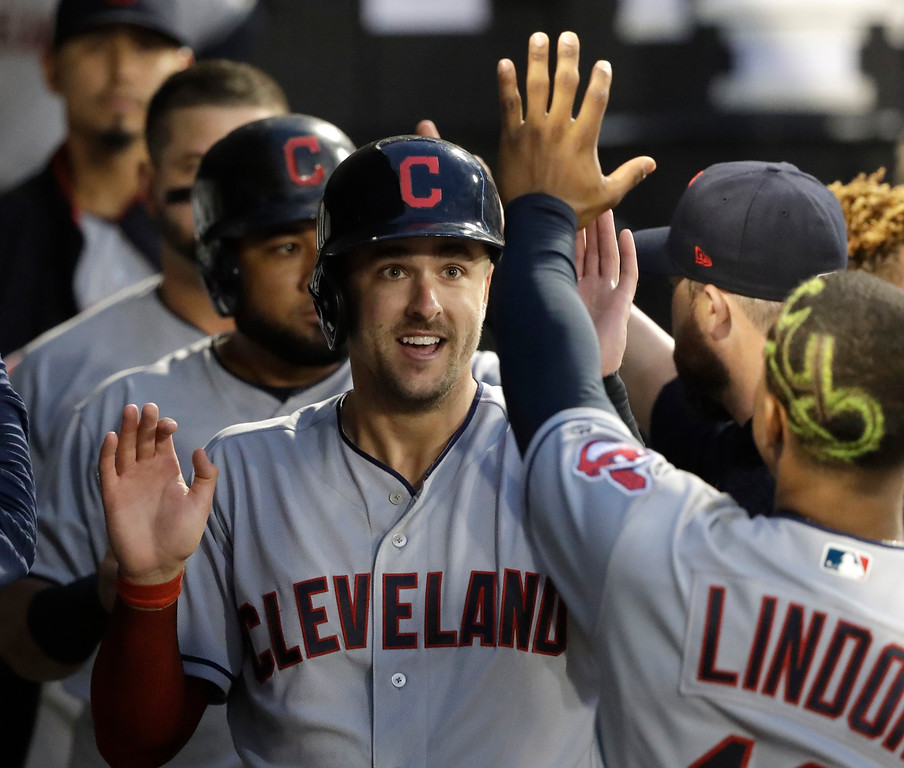 . Cleveland Indians\' Lonnie Chisenhall, left, celebrates in the dugout after scoring on a double by Yan Gomes during the fourth inning of a baseball game against the Chicago White Sox Monday, June 11, 2018, in Chicago. Melky Cabrera also scored on the play. (AP Photo/Charles Rex Arbogast)