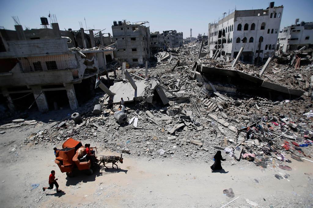 . Palestinians carry their belongings through the heavily bombed Gaza City neighborhood of Shijaiyah, close to the Israeli border, Friday, Aug. 1, 2014.  (AP Photo/Hatem Moussa, File)