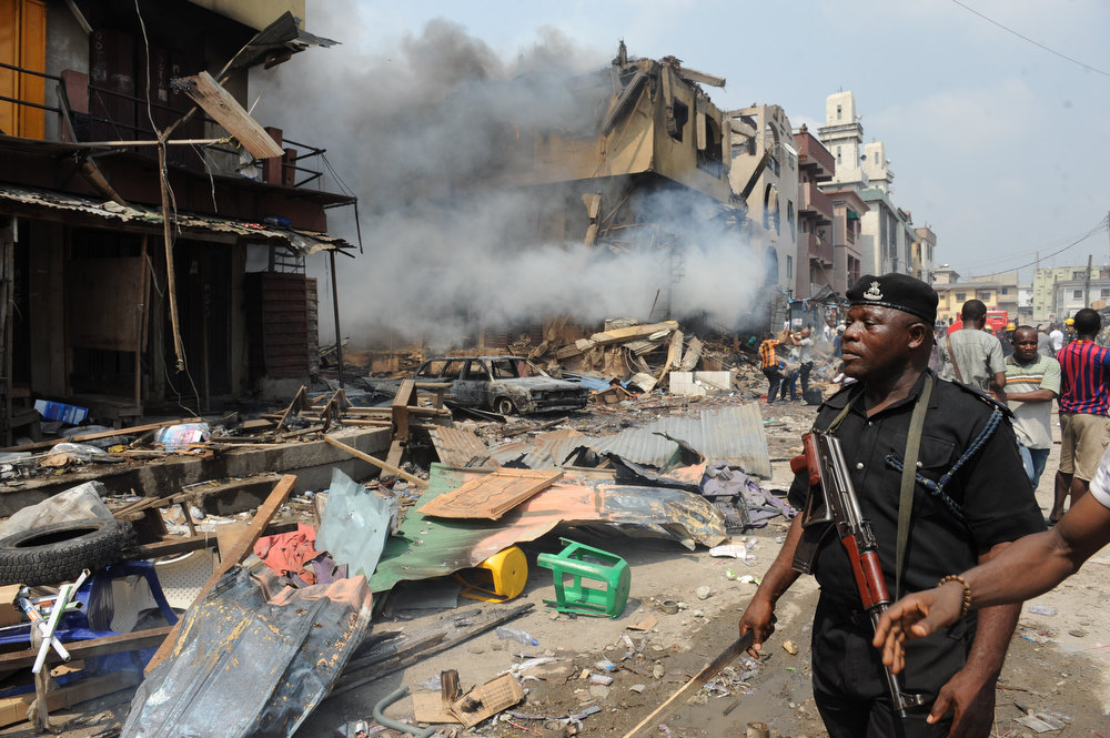 . A policeman looks at building stocked with fireworks on fire in Lagos on December 26, 2012.  Fire ripped through a crowded neighborhood in Nigeria\'s largest city and wounded at least 30 people after a huge explosion rocked a building believed to be storing fireworks, officials said.  AFP PHOTO/PIUS  UTOMI EKPEI/AFP/Getty Images