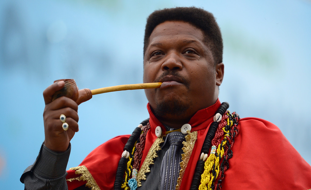 . Witchdoctor Chik Jeitoso smokes a pipe during a performance for the media at the Arena da Baixada stadium in Curitiba, Brazil, Wednesday, June 11, 2014. During the performance Jeitoso, a famous witchdoctor from Curitiba, predicted difficulties for Brazil in the World Cup and the bad energies are likely to affect Neymar and Messi during the competition. (AP Photo/Manu Fernandez)