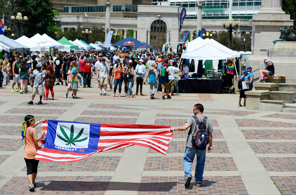 . Allison Vanderveen and her brother, Ryan Vanderveen, walk with a flag celebrating the pass of Amendment 64 during the Denver 420 Rally held Saturday at Civic Center Park. (Photo by Kira Horvath/ The Denver Post)