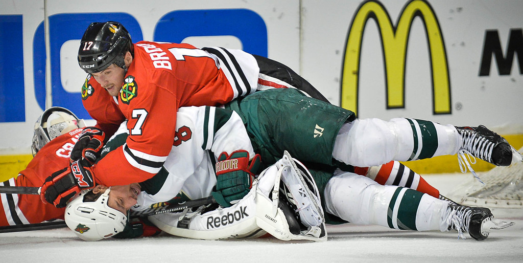 . Chicago\'s Sheldon Brookbank keeps his hands on the head of Minnesota\'s Cody McCormick after McCormick collided with Blackhawks goalie Corey Crawford during the second period.  (Pioneer Press: Ben Garvin)