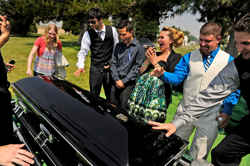 . Chantel Blunk, wife of Jonathan Blunk, third from the right, laughs with family and friends as they discover how hot the casket is while trying to leave handprints on it on Friday, August 03, 2012, at Mountain View Cemetery in Reno, Nevada.
