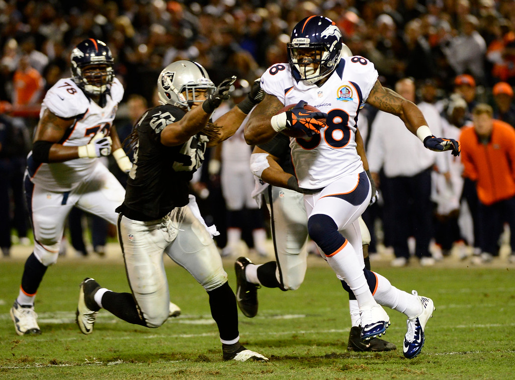 . Denver Broncos wide receiver Demaryius Thomas #88 picks up some yards as Oakland Raiders outside linebacker Philip Wheeler #52  moves in on defense during the first quarter  at the O.co Coliseum, in Oakland , CA December 06, 2012.      Joe Amon, The Denver Post