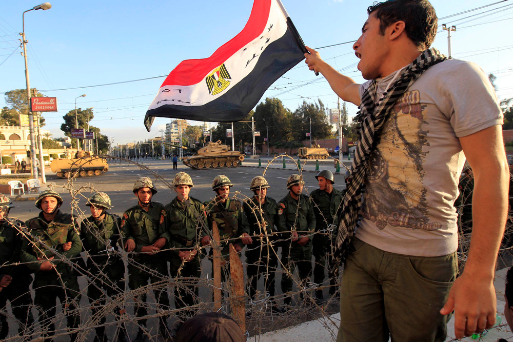 . A protester against Egypt\'s President Mohamed Mursi waves an Egyptian flag in front of Republican Guard soldiers standing behind a barbed wire barricade guarding the presidential palace in Cairo December 7, 2012. Tens of thousands of Egyptian protesters surged around the presidential palace on Friday and the opposition rejected Mursi\'s call for dialogue to end a crisis that has polarised the nation and sparked deadly clashes. REUTERS/Mohamed Abd El Ghany