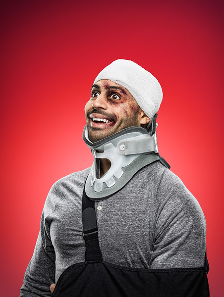 Smiling, bloody man with his head wrapped in bandages, wearing a neck brace and sling.