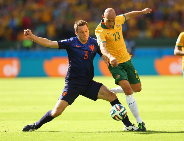 . Stefan de Vrij of the Netherlands and Mark Bresciano of Australia compete for the ball during the 2014 FIFA World Cup Brazil Group B match between Australia and Netherlands at Estadio Beira-Rio on June 18, 2014 in Porto Alegre, Brazil.  (Photo by Quinn Rooney/Getty Images)