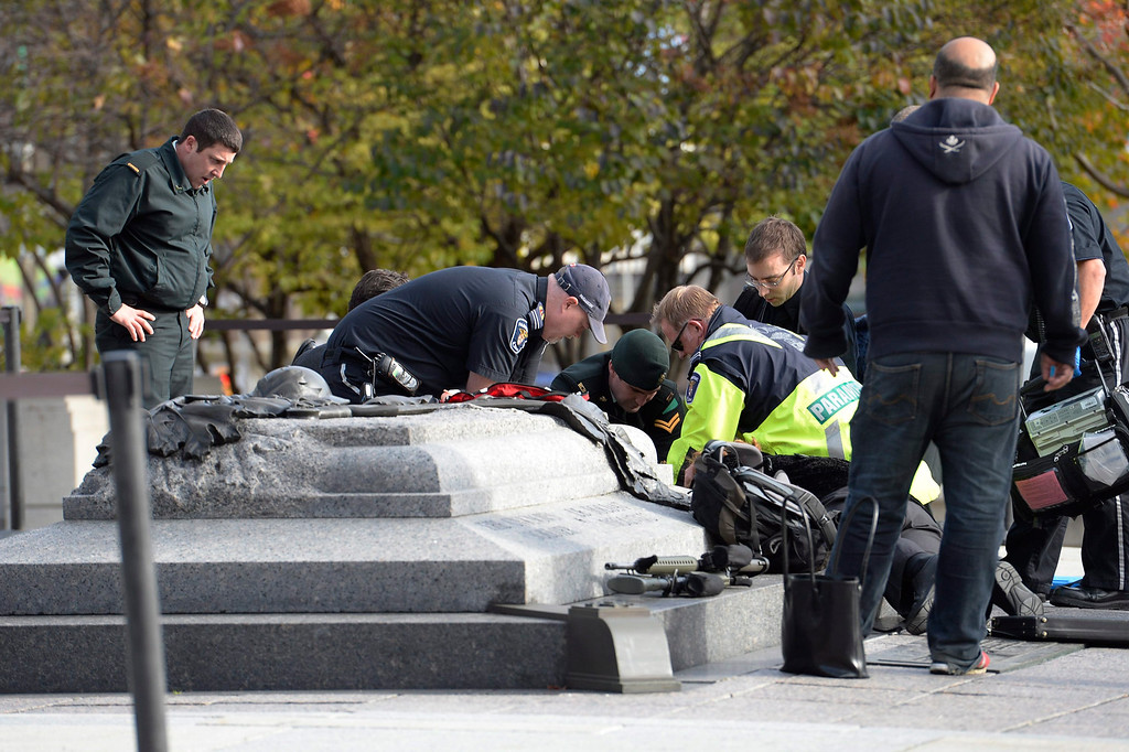 . Emergency personnel tend to a soldier shot at the National Memorial near Parliament Hill in Ottawa on Wednesday Oct. 22, 2014.  The soldier was standing guard when an unknown gunman shot him. The gunman reportedly ran towards Parliament Hill, which is currently under lockdown and surrounded by security.  Prime Minister Stephen Harper was rushed away from the building to an undisclosed location, officials in his office said. (AP Photo/The Canadian Press, Adrian Wyld)