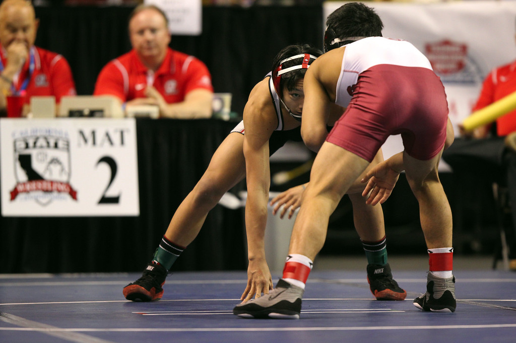 . James Logan\'s Jacob Macalolooy, left, wrestles Clovis West\'s Chris Garcia in a 138-pound consolation match during the California Interscholastic Federation wrestling championships in Bakersfield, Calif., on Saturday, March 2, 2013. Garcia would go onto win the match. (Anda Chu/Staff)