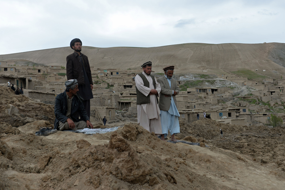 . Afghan villagers pray at the scene in Argo district of Badakhshan province on May 3, 2014 after a massive landslide May 2 buried a village. Rescuers searched in vain for survivors May 3 after a landslide buried an Afghan village, killing 350 people and leaving thousands of others feared dead amid warnings that more earth could sweep down the hillside. Local people made desperate efforts to find victims trapped under a massive river of mud that engulfed Aab Bareek village in Badakhshan province, where little sign remained of hundreds of destroyed homes. (SHAH MARAI/AFP/Getty Images)