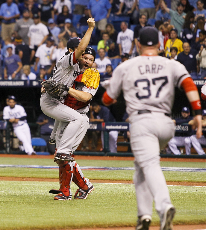. Boston Red Sox relief pitcher Koji Uehara jumps into the arms of catcher David Ross after striking out the Tampa Bay Rays\' Evan Longoria to win Game 4 of the American League Division Series at Tropicana Field in St. Petersburg, Florida, on Tuesday, October 8, 2013. Boston prevailed, 3-1, to clinch the series. (Will Vragovic/Tampa Bay Times/MCT)
