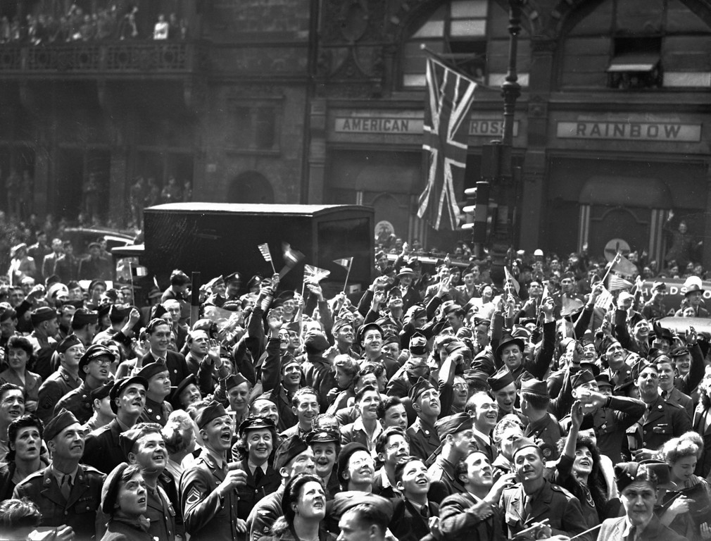 . British civilians and Allied service men and women gather, as part of a huge crowd, outside Rainbow Corner, the American Red Cross club, near Piccadilly Circus, London, May 7, 1945, to hear the final announcement of Germany\'s total surrender. (AP Photo)