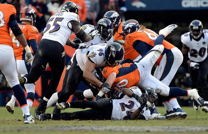 . Denver Broncos running back Jacob Hester (40) gets stopped after taking a hand off from Denver Broncos quarterback Peyton Manning (18) during the first half.  The Denver Broncos vs Baltimore Ravens AFC Divisional playoff game at Sports Authority Field Saturday January 12, 2013. (Photo by Hyoung Chang,/The Denver Post)