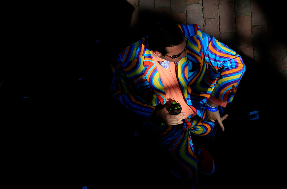 Description of . A man in a colorful suit dances prior to the 140th running of the Kentucky Derby at Churchill Downs on May 3, 2014 in Louisville, Kentucky.  (Photo by Jamie Squire/Getty Images)
