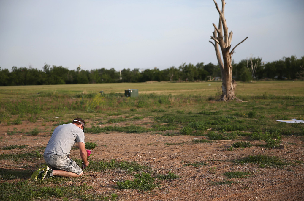 . David Friess remembers his lost pets as he puts flowers in the ground where his house used to be and his pet was found in the rubble one year ago when a tornado passed through the area on May 20, 2014 in Moore, Oklahoma.  On May 20, 2013 a two-mile wide EF5 tornado touched down in the town killing 24 people and leaving behind extensive damage to homes and businesses.  (Photo by Joe Raedle/Getty Images)