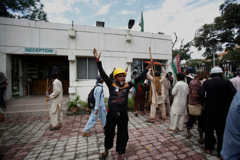 . Pakistani protesters hold sticks and chant slogans after intruding into the state television building in Islamabad, Pakistan, Monday, Sept. 1, 2014. Anti-government protesters and Pakistani police have clashed once again as the demonstrators pushed into a sprawling government complex in the country\'s capital in an effort to try to reach the prime minister\'s official residence. (AP Photo/Anjum Naveed)