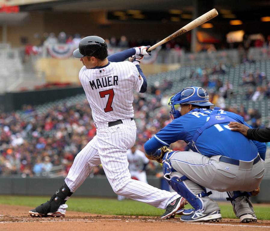 . Minnesota Twinsí Joe Mauer follows through with a base hit off Kansas City Royals pitcher Jason Vargasmduring the first inning.  Royals catcher Salvador Perez awaits the pitch. (AP Photo/Tom Olmscheid)