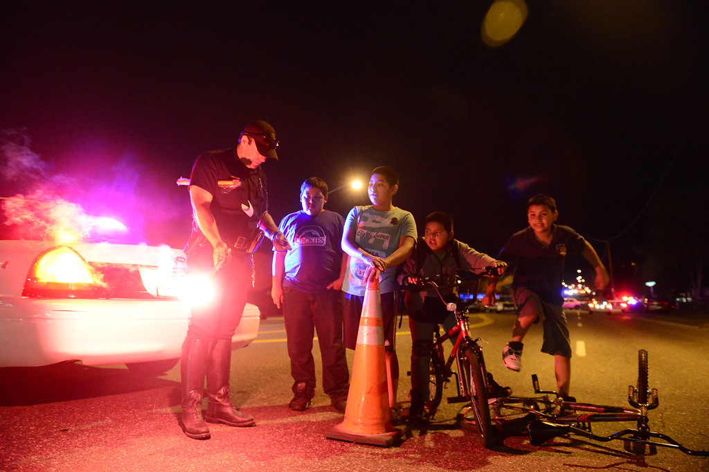 . DENVER, CO - MAY 14: Traffic officer Luke Palmatier lights a flare as a group of neighborhood youths look on as police investigate the scene of an officer-involved shooting near the intersection of Harvard and Federal Boulevard. (Photo by AAron Ontiveroz/The Denver Post)