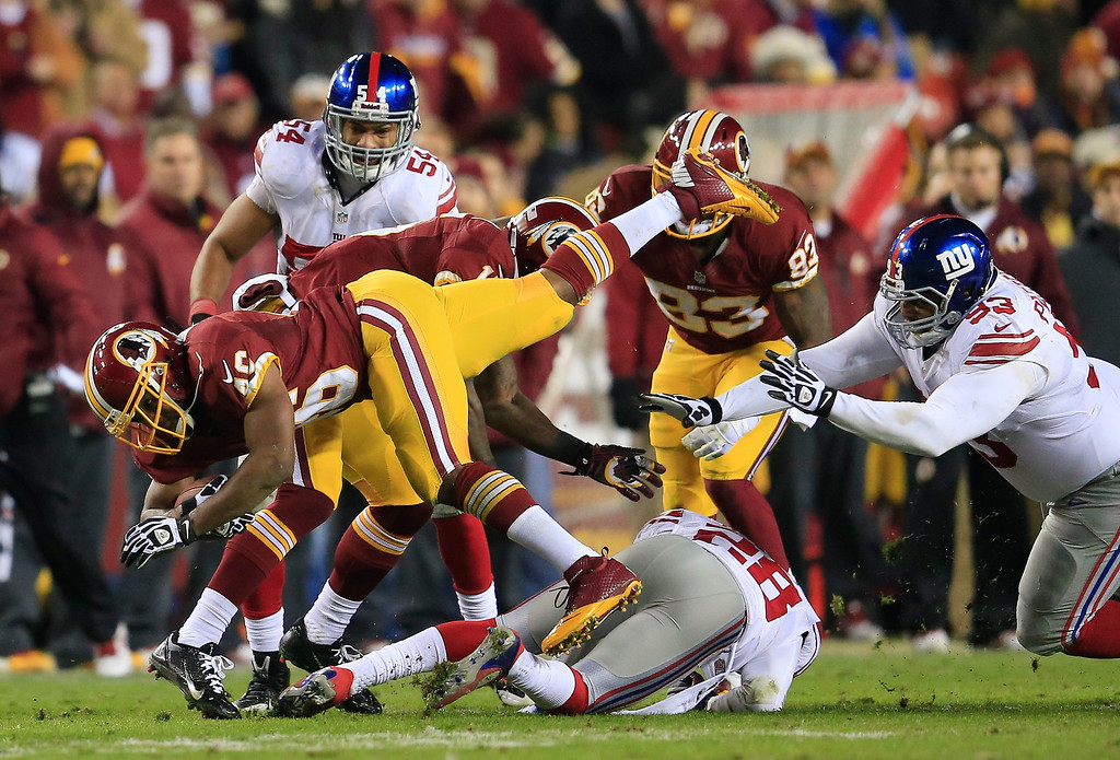. Running back Alfred Morris #46 of the Washington Redskins is tackled by Jayron Hosley #28 and defensive tackle Mike Patterson #93 of the New York Giants during the second half of the Giants 24-17 win at FedExField on December 1, 2013 in Landover, Maryland.  (Photo by Rob Carr/Getty Images)