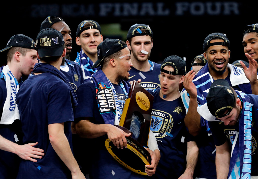 . Villanova\'s Jalen Brunson holds the championship trophy as he celebrates with his teammates after the championship game of the Final Four NCAA college basketball tournament against Michigan, Monday, April 2, 2018, in San Antonio. Villanova won 79-62. (AP Photo/David J. Phillip)