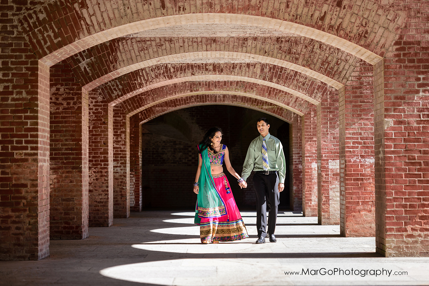 Indian couple holding hands and walking in the brick hallway during engagement session at San Francisco Fort Point