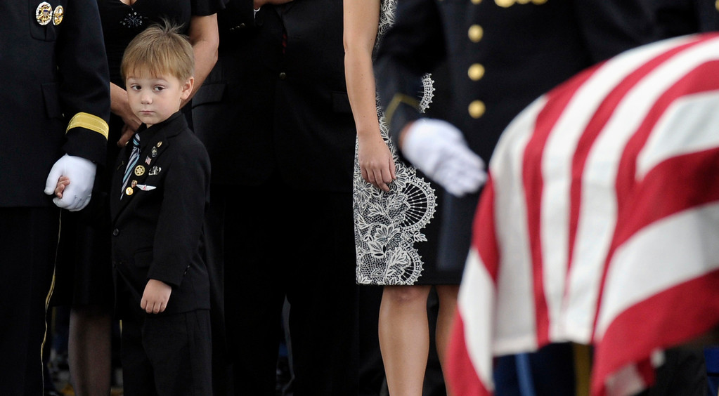 . Kaden Bowden, son of U.S. Army Staff Sgt. Joshua J. Bowden, looks at the casket for his father during burial services for Staff Sgt. Bowden at Arlington National Cemetery in Arlington, Va., Friday, Sept. 27, 2013. Bowden was from Villa Rica, Ga., and died on Aug. 31, 2013, from injuries sustained while serving in Afghanistan. (AP Photo/Susan Walsh)
