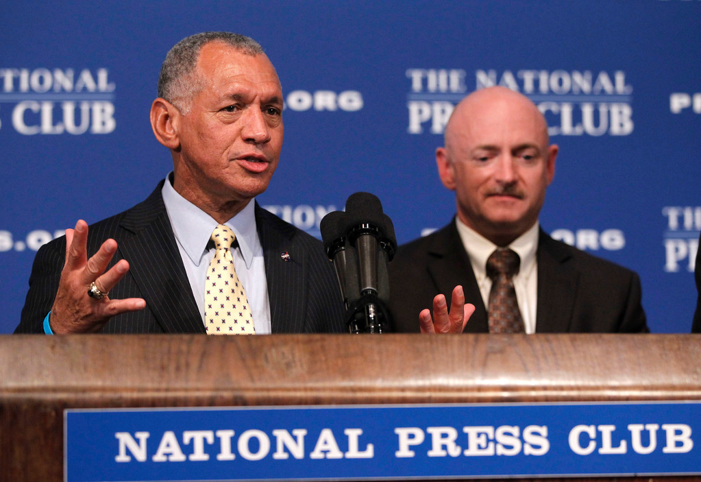 . NASA Administrator Charles Bolden, left, accompanied by astronaut Capt. Mark Kelly, husband of wounded Rep. Gabrielle Giffords, D-Ariz., speaks at the National Press Club in Washington, Friday, July 1, 2011. (AP Photo/Charles Dharapak)