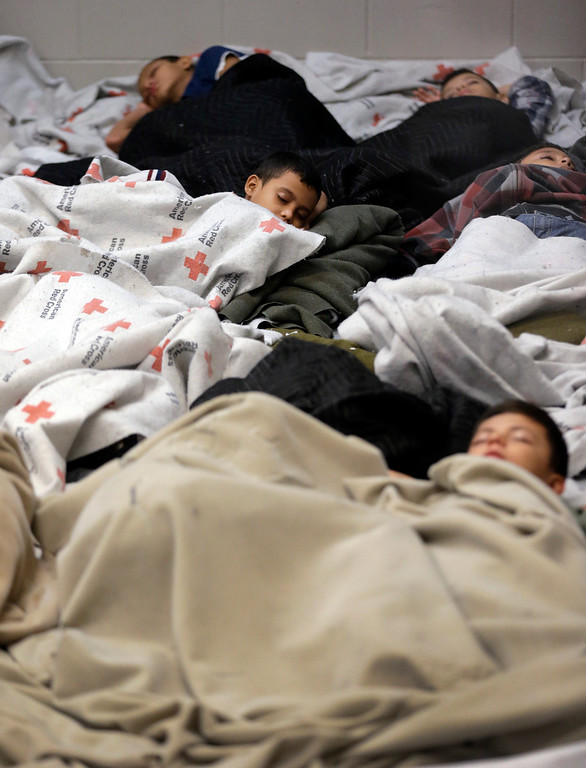 . A detainees sleep in a holding cell at a U.S. Customs and Border Protection processing facility, Wednesday, June 18, 2014, in Brownsville,Texas. (AP Photo/Eric Gay, Pool)
