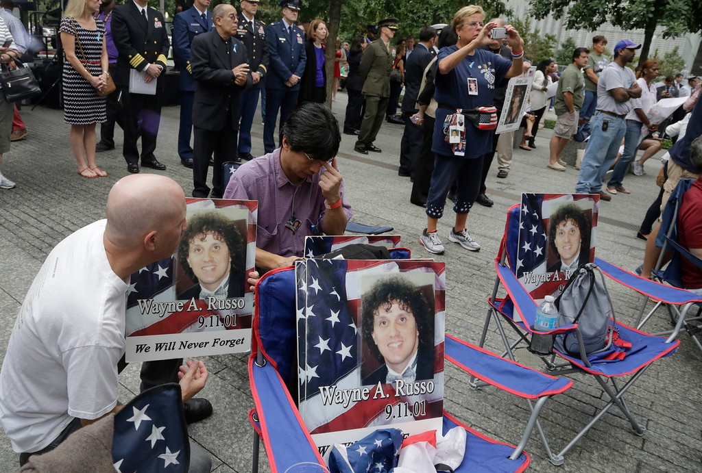 """. Brian Sommer, left, and Lito Deleon hold photos of their friend Wayne Russo, who died in the Sept 11, 2001 attacks, during memorial observances held at the site of the World Trade Center in New York, Thursday, Sept. 11, 2014. The three played together in the punk rock band \""""Stetz\"""" in Union , N.J. in the 1980\'s. (AP Photo/Mark Lennihan, Pool)"""