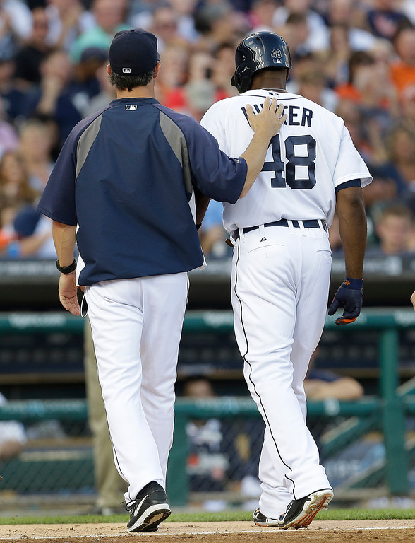 . Detroit Tigers manager Brad Ausmus puts his hand on Torii Hunter\'s back as they head to the dugout after Hunter hit a single against the Kansas City Royals in the fourth inning of a baseball game in Detroit, Monday, June 16, 2014.  (AP Photo/Paul Sancya)