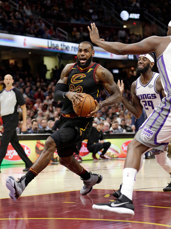 . Cleveland Cavaliers\' LeBron James, left, drives against the Sacramento Kings in the first half of an NBA basketball game, Wednesday, Dec. 6, 2017, in Cleveland. (AP Photo/Tony Dejak)