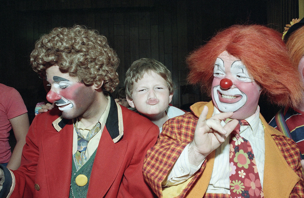 . Kevin Thompson, celebrating his fourth year in Ringling Bros. Barnum and Bailey\'s famed Clown Alley, watches as 9-year-old Jonathon Young tries his hand at clowning during a visit by the circus troupe to Temple Beth Solomon of the Deaf in Arleta, California, Sept. 14, 1984. (AP Photo/Liu Heung Shing)