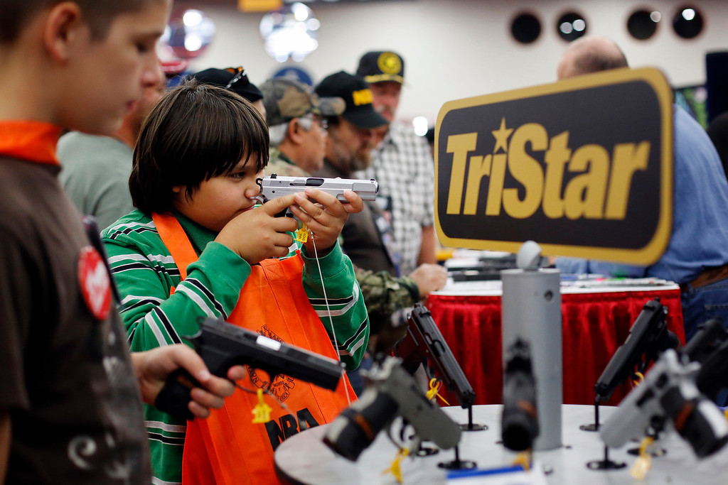 . Brothers, 10-year-old Kayden La, center. and 13-year-old Jacob La, left, inspect pistols at a booth, during the NRA Annual Meeting of Members at the National Rifle Association\'s 142 Annual Meetings and Exhibits in the George R. Brown Convention Center Saturday, May 4, 2013, in Houston. National Rifle Association leaders told members Saturday that the fight against gun control legislation is far from over, with battles yet to come in Congress and next year\'s midterm elections, but they vowed that none in the organization will ever have to surrender their weapons. (AP Photo/Houston Chronicle, Todd Spoth)