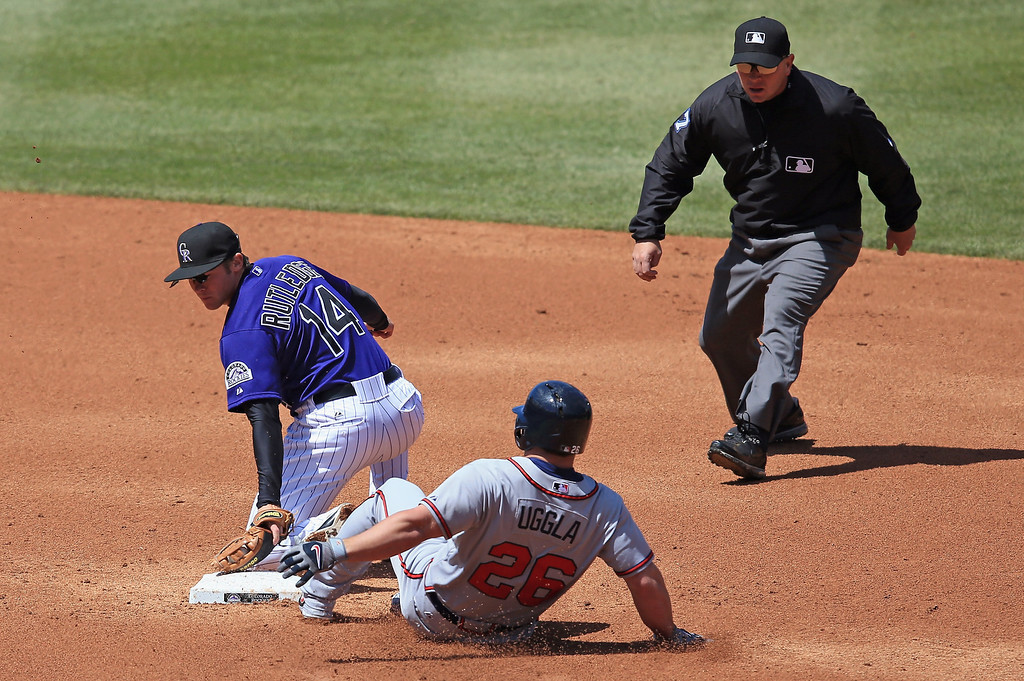 . Dan Uggla #26 of the Atlanta Braves slide safely into second base with a double ahead of the tag by second baseman Josh Rutledge #14 of the Colorado Rockies as umpire Scott Barry oversees the play in the second inning at Coors Field on April 24, 2013 in Denver, Colorado.  (Photo by Doug Pensinger/Getty Images)