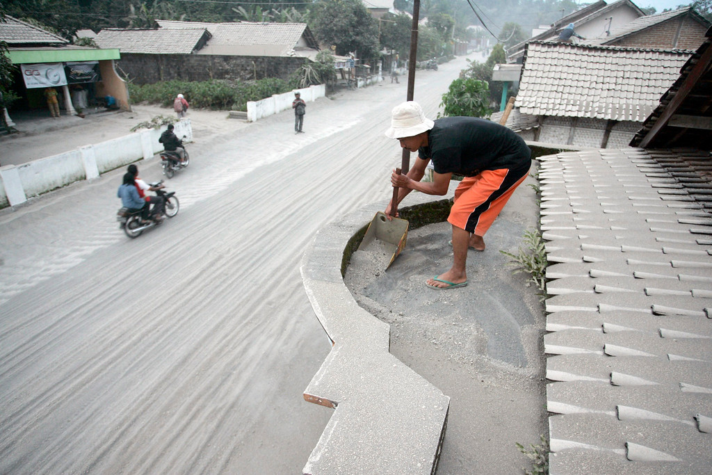 . An Indonesian villager cleans up volcanic ash and sand from the Mount Kelud eruption on the roof of his house at Sugihwaras village in Kediri, East Java, Indonesia, 14 February 2014.   EPA/FULLY HANDOKO