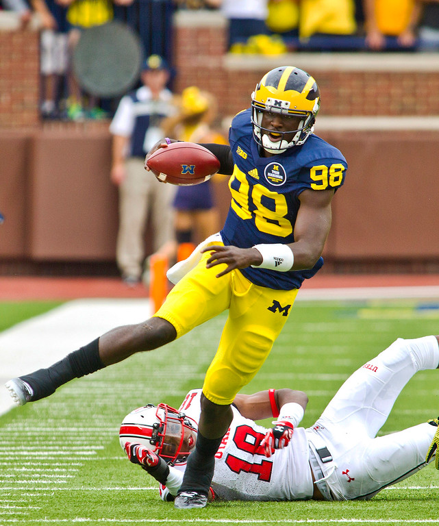 . Michigan quarterback Devin Gardner (98) escapes a tackle attempt from Utah defensive back Eric Rowe (18) in the first quarter of an NCAA college football game in Ann Arbor, Mich., Saturday, Sept. 20, 2014. (AP Photo/Tony Ding)