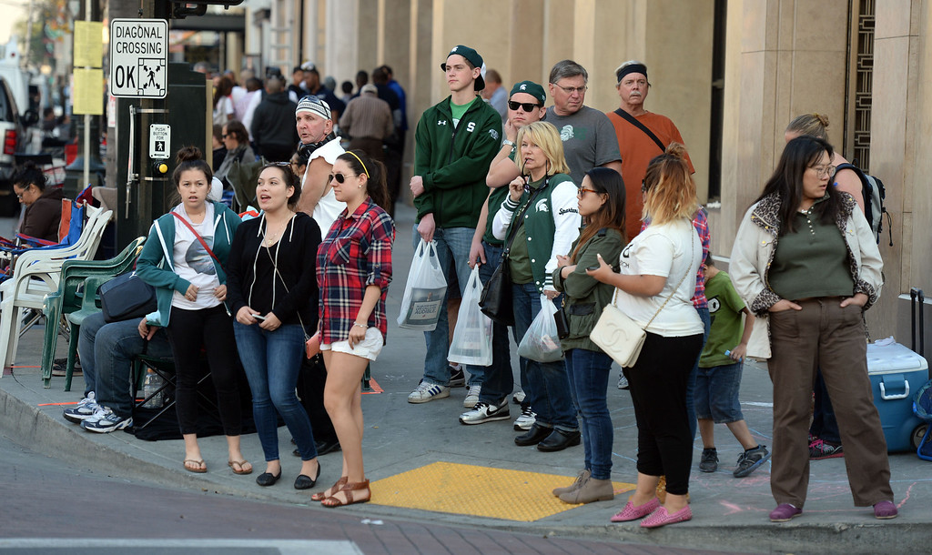 . people camp out and stake their spots as others shop prior to the Rose Parade along Colorado Boulevard in Pasadena, Calif., on Tuesday, Dec. 29, 2013.     (Keith Birmingham Pasadena Star-News)